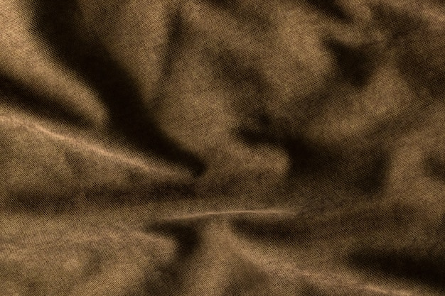 Top view of empty, abstract template - crumpled dense fabric of a dark brown hue with waves and folds background and texture. Premium Photo