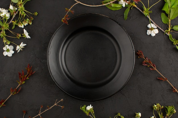 Top view empty black plate along with white flowers on the dark floor Free Photo