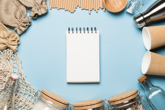 Top view empty notepad with eco friendly objects Free Photo