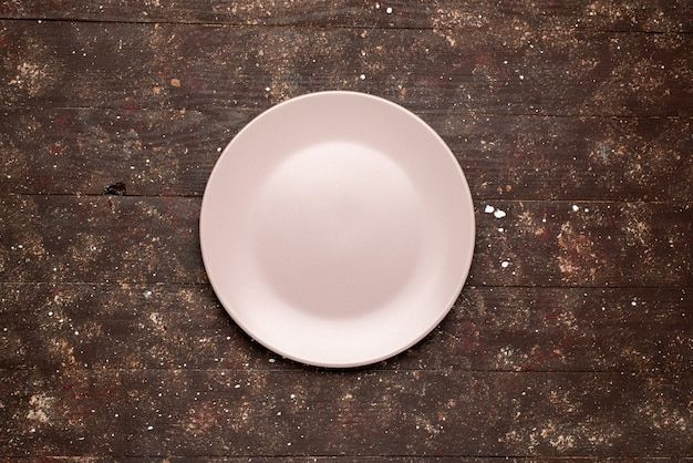 Top view of empty pink plate isolated on brown rustic, wood plate wooden Free Photo