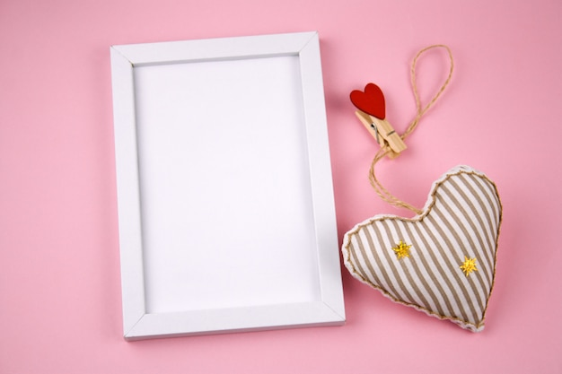 Top view empty white wooden frame  and fabric soft toy in a shape of heart pastel pink background Premium Photo