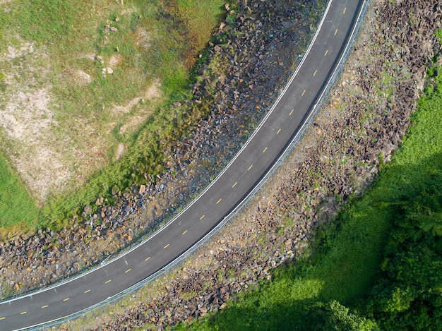Top view an empty winding tarmac road with green trees and grass om roadside from drone aerial view from above. Premium Photo