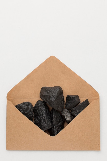 Top view envelope filled with coal ore Free Photo