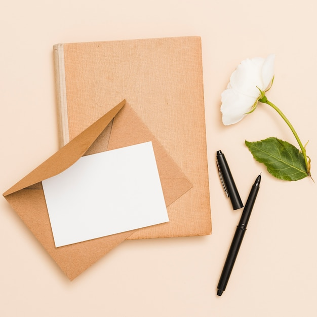 Top view of envelope, flower and book Free Photo