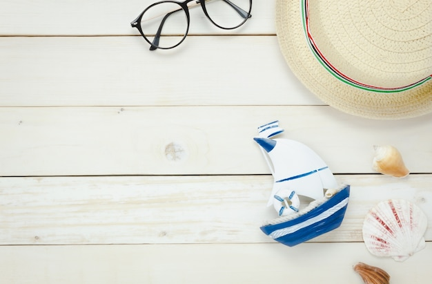 Top view essential travel summer items.the boat eyeglasses  hat shell on white  wooden background. Free Photo