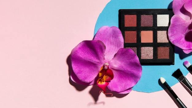 Top view of eye shadow and flowers on pink background Free Photo