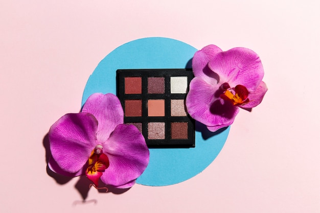 Top view of eye shadow and flowers with pink background Free Photo