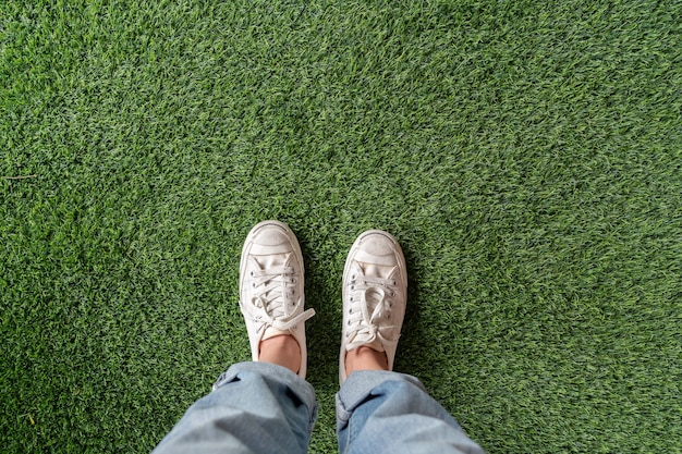 Top view of female feet with sneakers standing on  green artificial grass Premium Photo