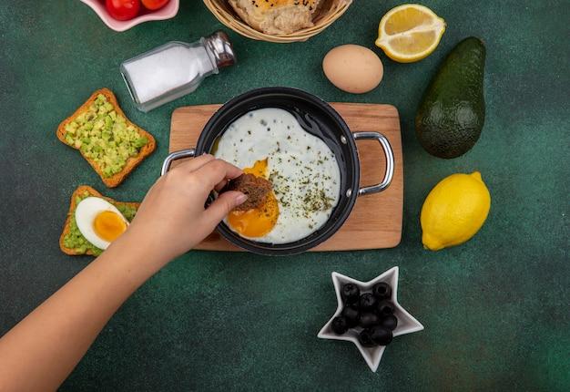 Vista dall'alto della femmina mano azienda fetta di pane con uovo fritto in padella sulla cucina in legno bordo con olive nere saliera limone toast pane con polpa di avocado su gre Foto Gratuite