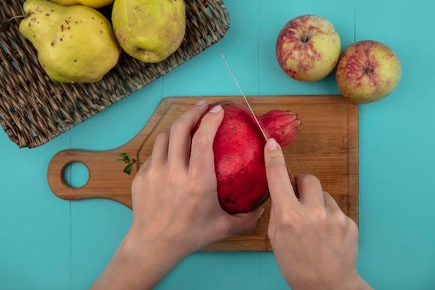 Vista dall'alto delle mani femminili che tagliano il melograno fresco su una tavola di cucina in legno con coltello su sfondo blu Foto Gratuite