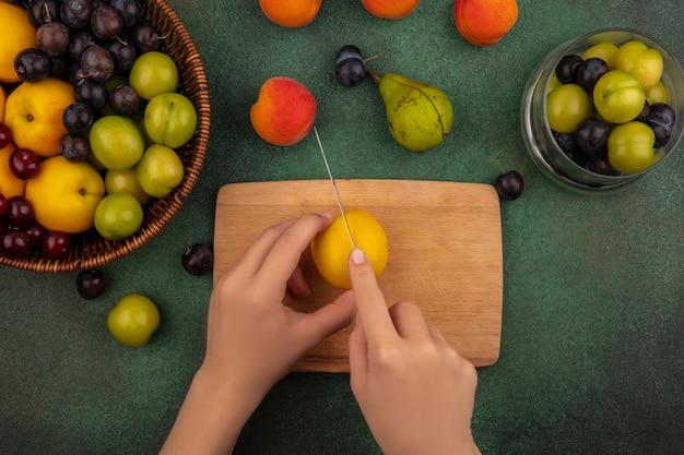 Vista dall'alto delle mani femminili che tagliano la pesca gialla con il coltello su una tavola di cucina in legno su uno sfondo verde Foto Gratuite