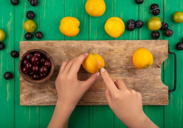 Vista dall'alto delle mani femminili che tagliano la pesca gialla con il coltello su una tavola di cucina in legno con ciliegie rosse su sfondo verde Foto Gratuite