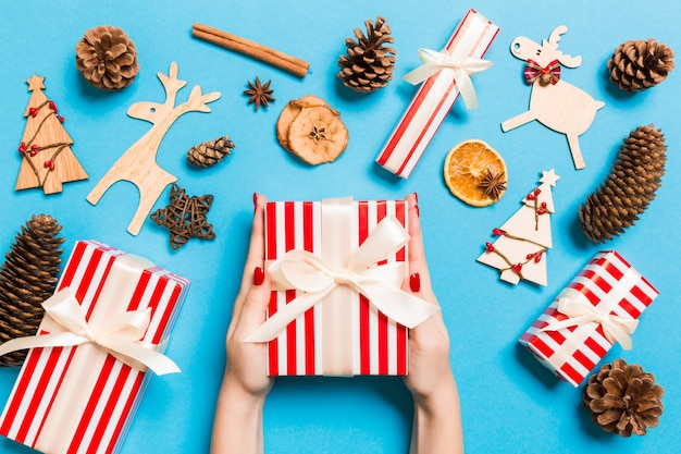 Top view of female hands holding a christmas present on festive blue background Premium Photo