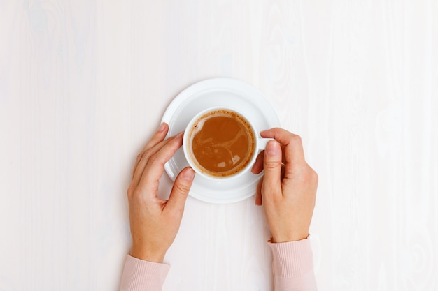 Top view on female hands holding a cup of coffee with milk at the table. Premium Photo