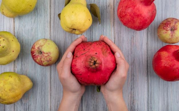 Vista dall'alto delle mani femminili che tengono melograno fresco rosso su un fondo di legno grigio Foto Gratuite