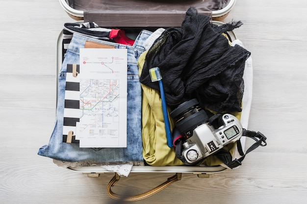 Top view of female's travelling bag with camera, brush and map Free Photo