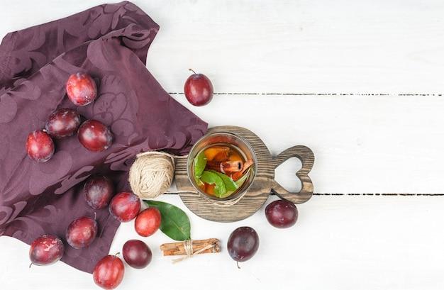 白い木の板の表面にシナモン、クルー、バーガンディのテーブルクロスと上面の発酵飲料。 無料写真