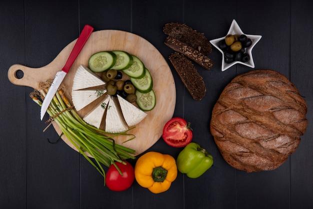 上面図フェタチーズ、オリーブ、キュウリ、ネギ、ピーマン、スタンドにナイフ、黒の背景に黒のパン 無料写真