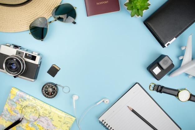 Top view, film camera, map, passport, smartphone, compass, sunglasses, notebook, purse with copy space. Premium Photo
