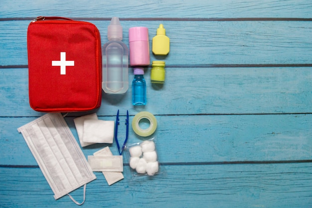 Top view first aid bag kid with medical supplies on wood Premium Photo