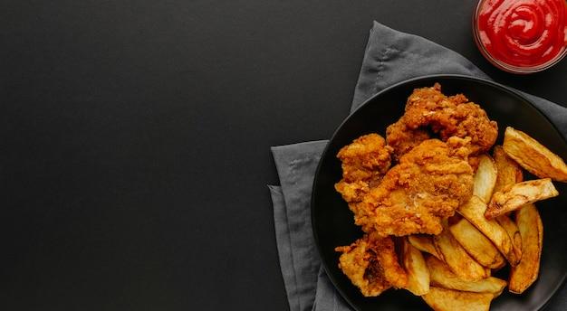 Vista dall'alto di pesce e patatine fritte sulla piastra con copia spazio Foto Gratuite
