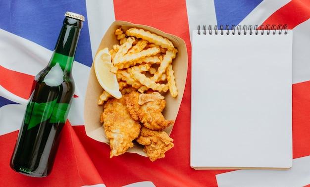 Vista dall'alto di pesce e patatine fritte sulla piastra con il taccuino e la bottiglia di birra Foto Gratuite