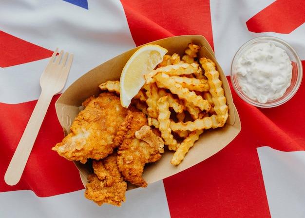 Vista dall'alto di fish and chips con fetta di limone e bandiera della gran bretagna Foto Gratuite