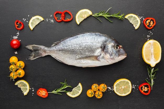 Vista dall'alto pesce e disposizione di condimento Foto Gratuite