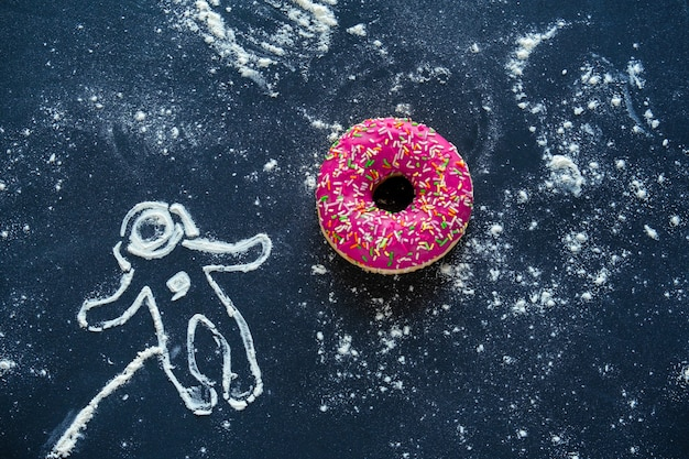 Top view flat lay creative still life with pink donut and spaceman made from flour on black Premium Photo