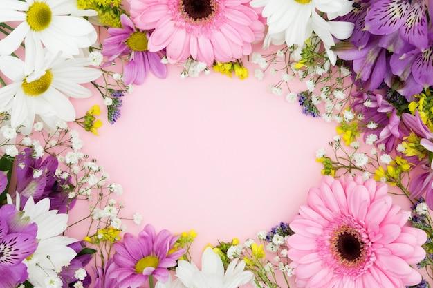 Вид сверху цветочная рамка с розовым фоном Premium Фотографии
