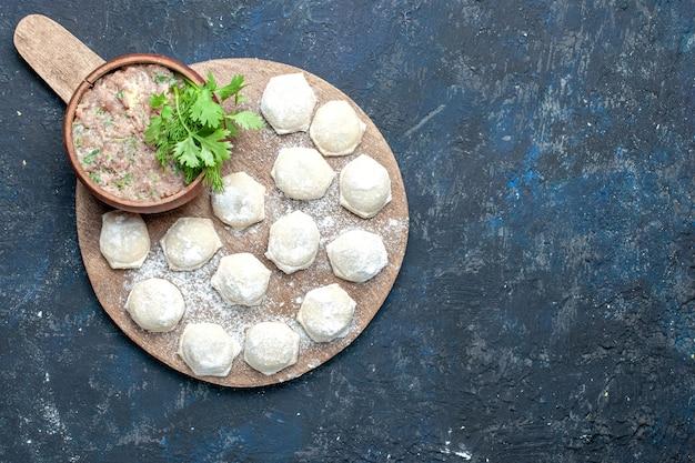 Vista dall'alto di pezzi di pasta infarinata con verdure di carne macinata sulla scrivania scura, pasta per la cena a base di carne cruda Foto Gratuite