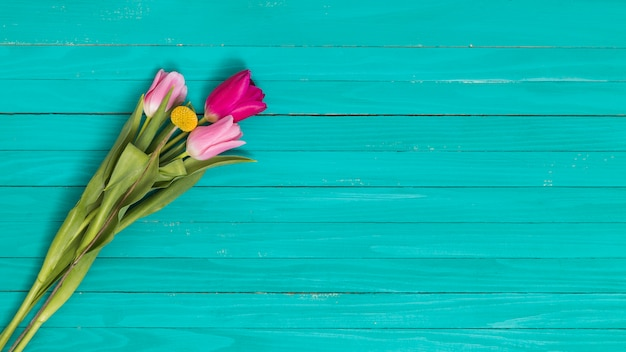 Top view of flowers against green wooden desk Free Photo