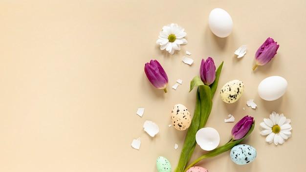 テーブルの上に配置されたトップビューの花と塗装卵 無料写真