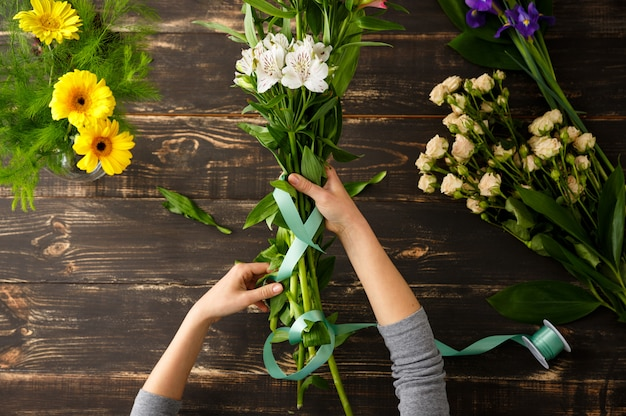 Top view of flowers, florist in process of making bouquet Free Photo