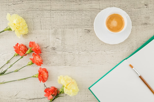 Top view flowers with book and coffee on wooden background Free Photo