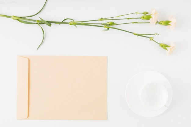 Top view flowers with envelope and cup Free Photo