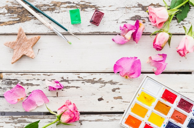 Top view flowers with painting material on wooden table Free Photo