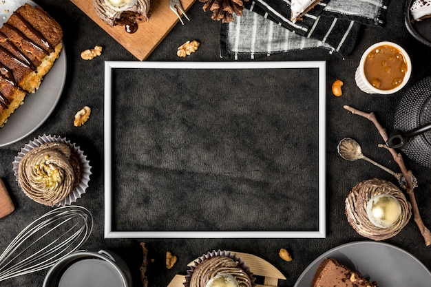 Top view of frame with cake and cupcakes Free Photo