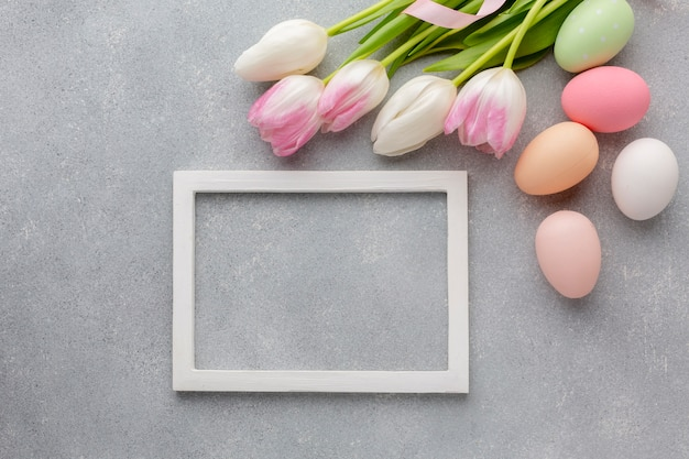 Top view of frame with colorful easter eggs and beautiful tulips Free Photo