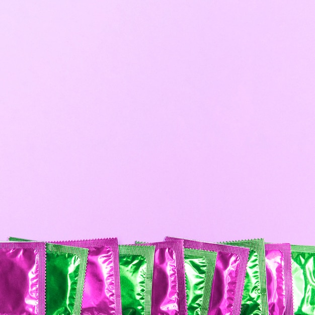Top view frame with green and pink condoms Free Photo