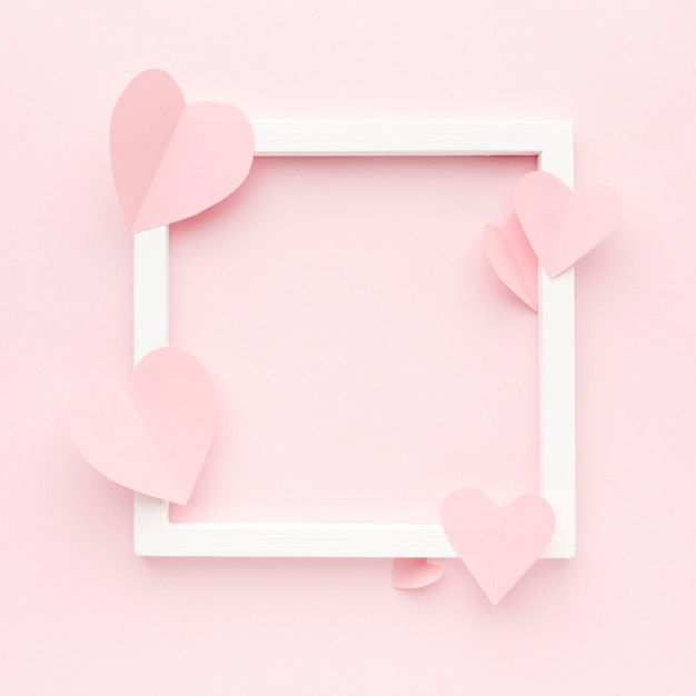 Top view frame with paper heart shapes Free Photo