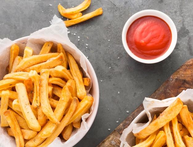Vista dall'alto di patatine fritte in una ciotola con salsa ketchup Foto Gratuite