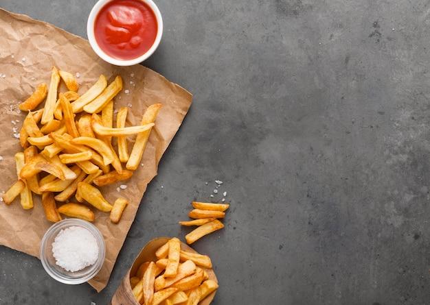 Vista dall'alto di patatine fritte su carta con sale e copia spazio Foto Gratuite