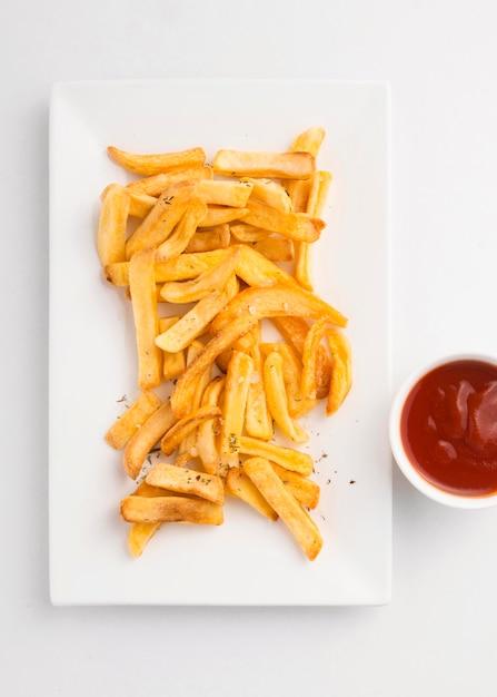 Vista dall'alto di patatine fritte sulla piastra con salsa ketchup Foto Gratuite