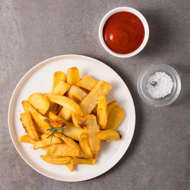 Vista dall'alto di patatine fritte con ketchup e sale Foto Gratuite