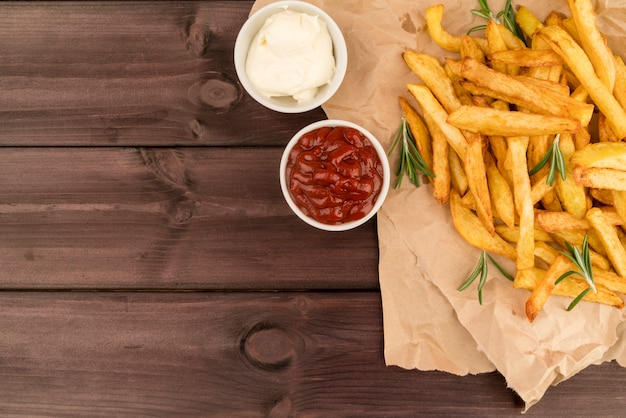 Вид сверху картофель фри с соусом на деревянный стол Premium Фотографии