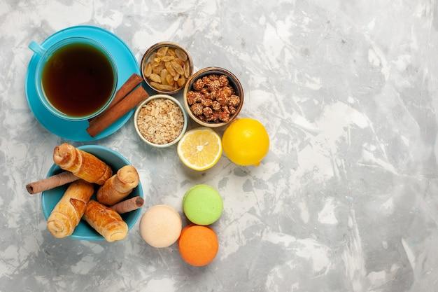 Vista dall'alto macarons francesi con una tazza di ciambelle di tè sulla superficie bianca Foto Gratuite