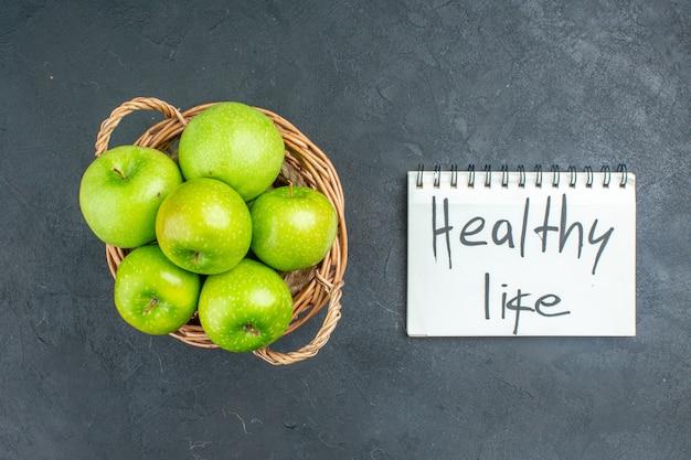 暗い表面のメモ帳に書かれた籐のバスケットの健康的な生活の上面図新鮮なリンゴ 無料写真