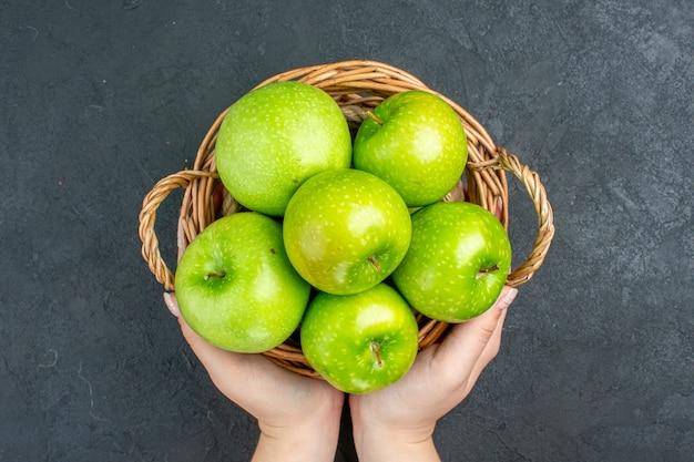 暗い表面の女性の手で籐のバスケットに新鮮なリンゴの上面図 無料写真