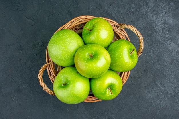 暗い表面の空きスペースに籐のバスケットに新鮮なリンゴの上面図 無料写真